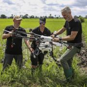Three operators work on a drone in the middle of a grassy field.