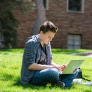 A student works on a laptop while sitting outdoors