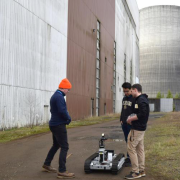 Michael Miles and Daniel Torres talk with another challenge participant during a break outside of the DARPA Subterranean Challenge course area.