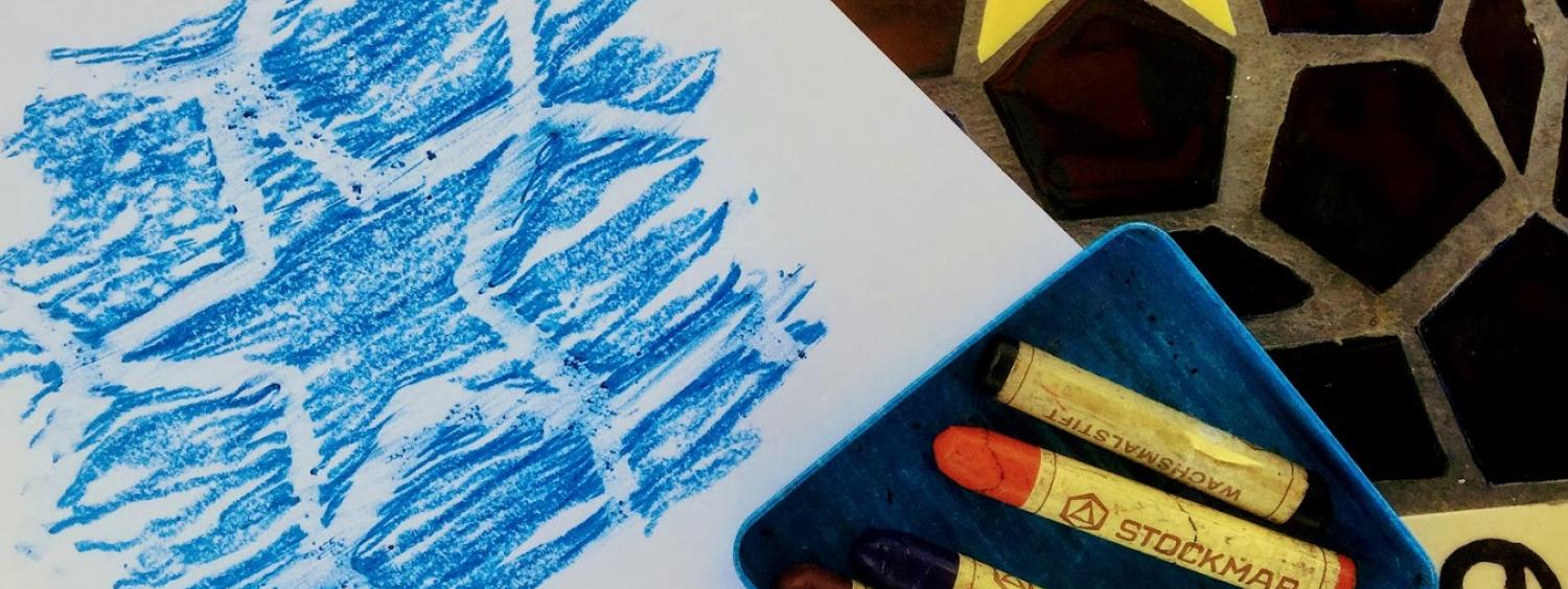 Crayons and a blue crayon rubbing of a star
