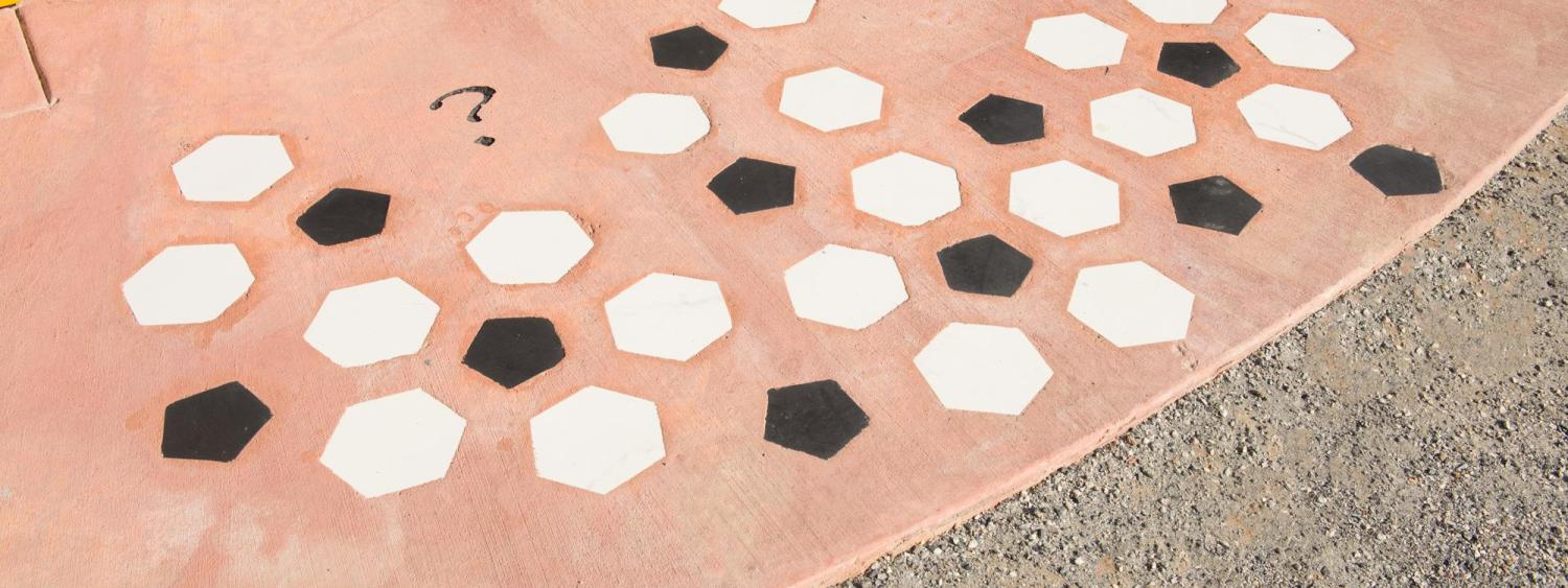 A group of white and black hexagons are seen on a red rock background.