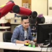 Student sits at a computer underneath a robotic arm