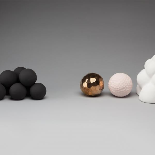 four ceramic forms on a grey background