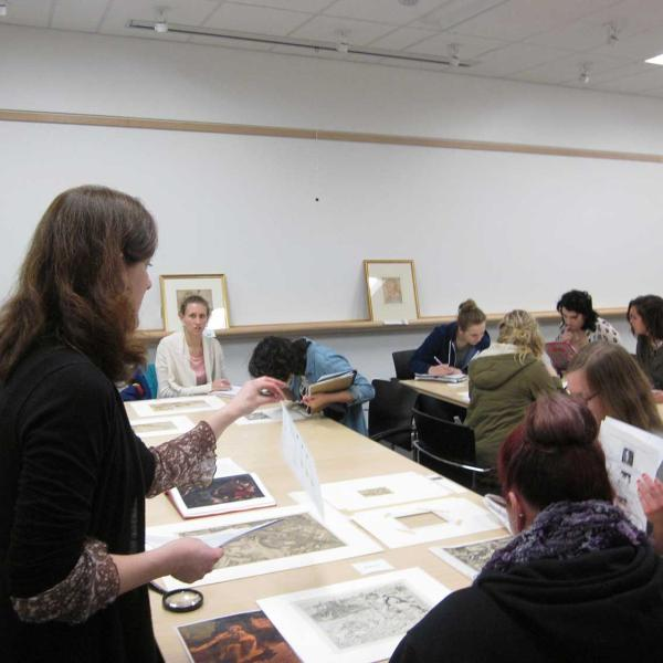 Woman gesturing to prints laying out on a table while speaking to a group of students