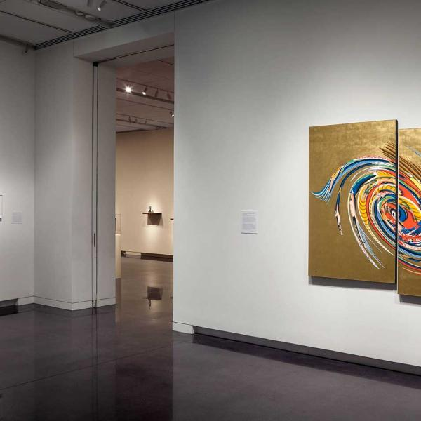 Installation view of diptych painting, gold with multi-color swirls
