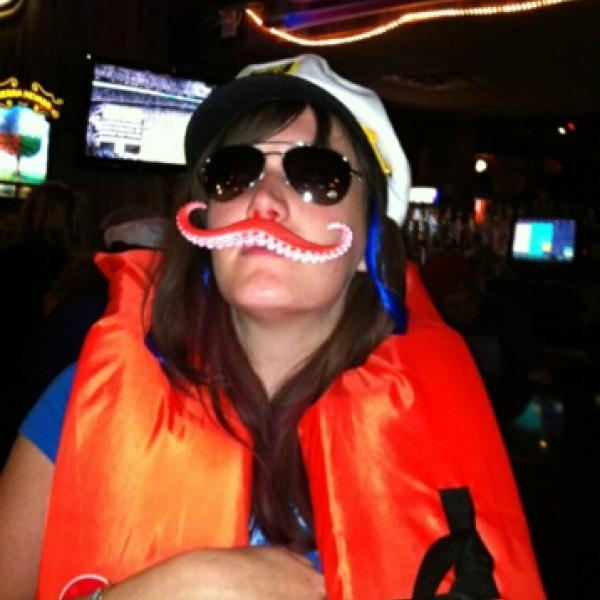 A woman wearing a life vest, sunglasses, and fake mostache.