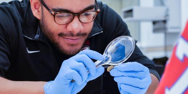 A male student uses a magnifying glass to look at the details of a gold coin