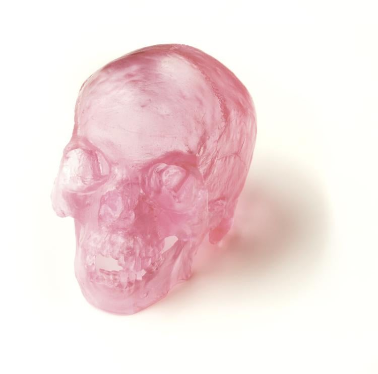 A skull cast in pink glass