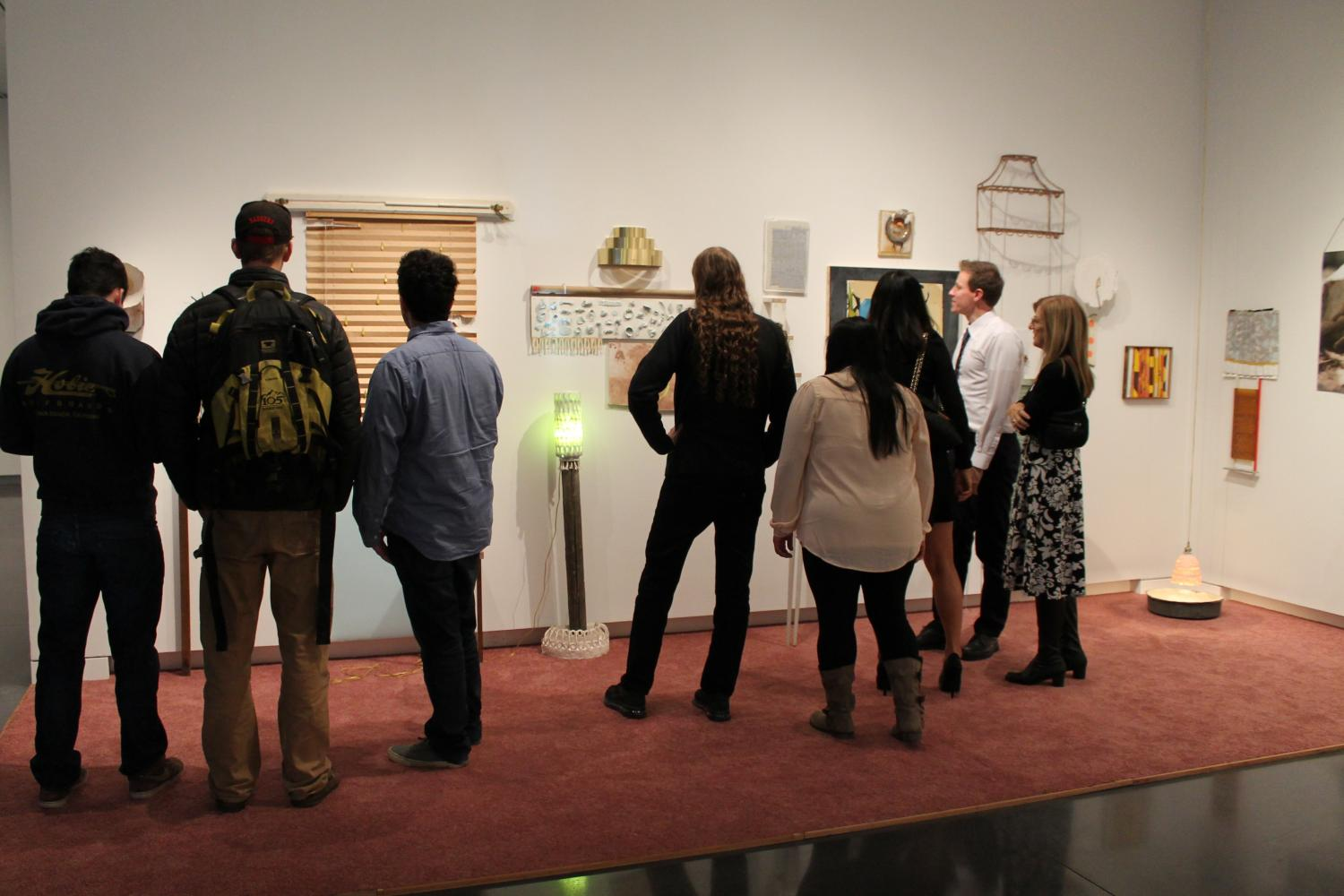 a group of people viewing objects on the wall of the gallery.