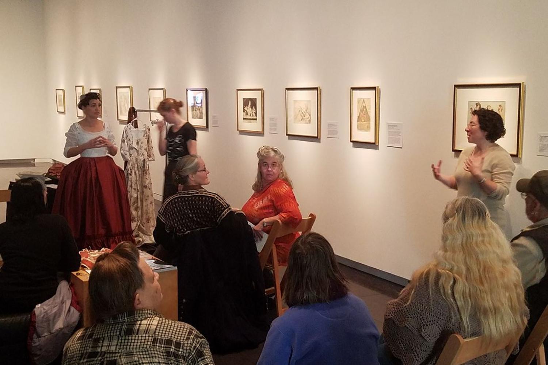 Women speaking in an exhibition of prints