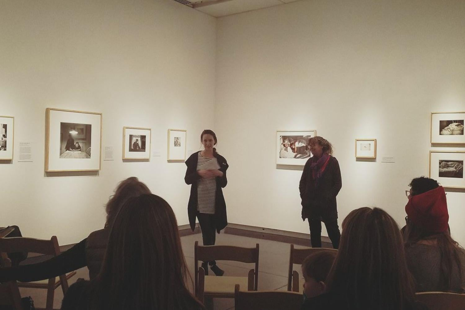 Women speaking in an exhibition of photographs