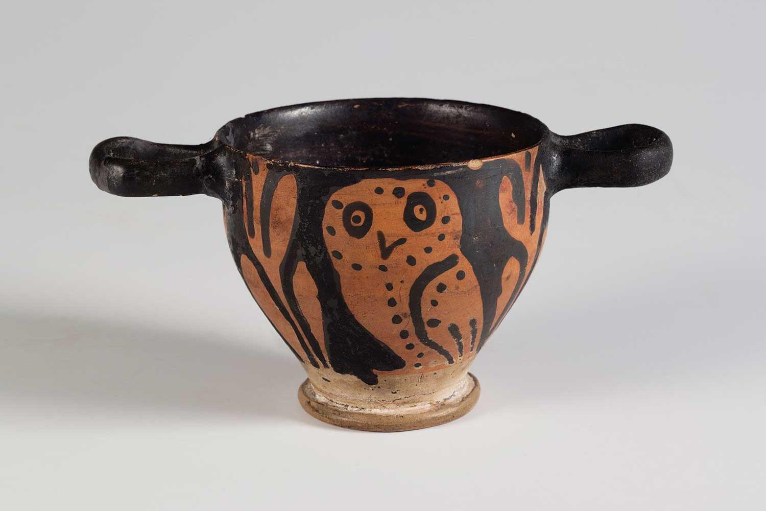 Small black cup with a horizontal handle on each side of the rim, decorated with orange owl.