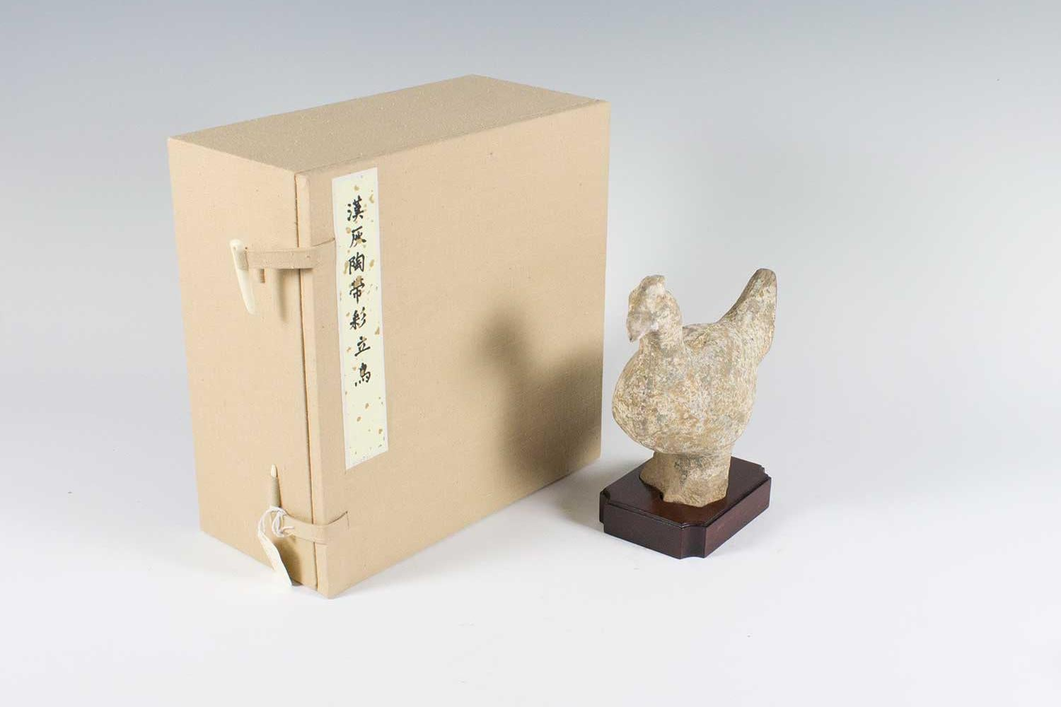 Clay figure of a small chicken standing on a wooden stand with tan box on left.