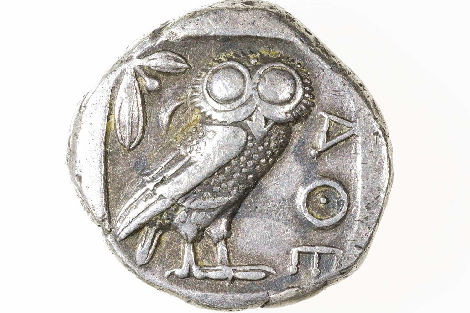 Silver coin depicting owl in center, olive branch on the top left, and Greek AOE on side