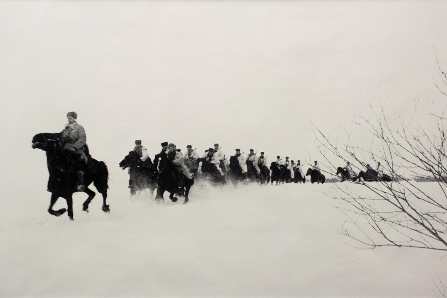 black and white photo of soldiers on horseback riding in the snow