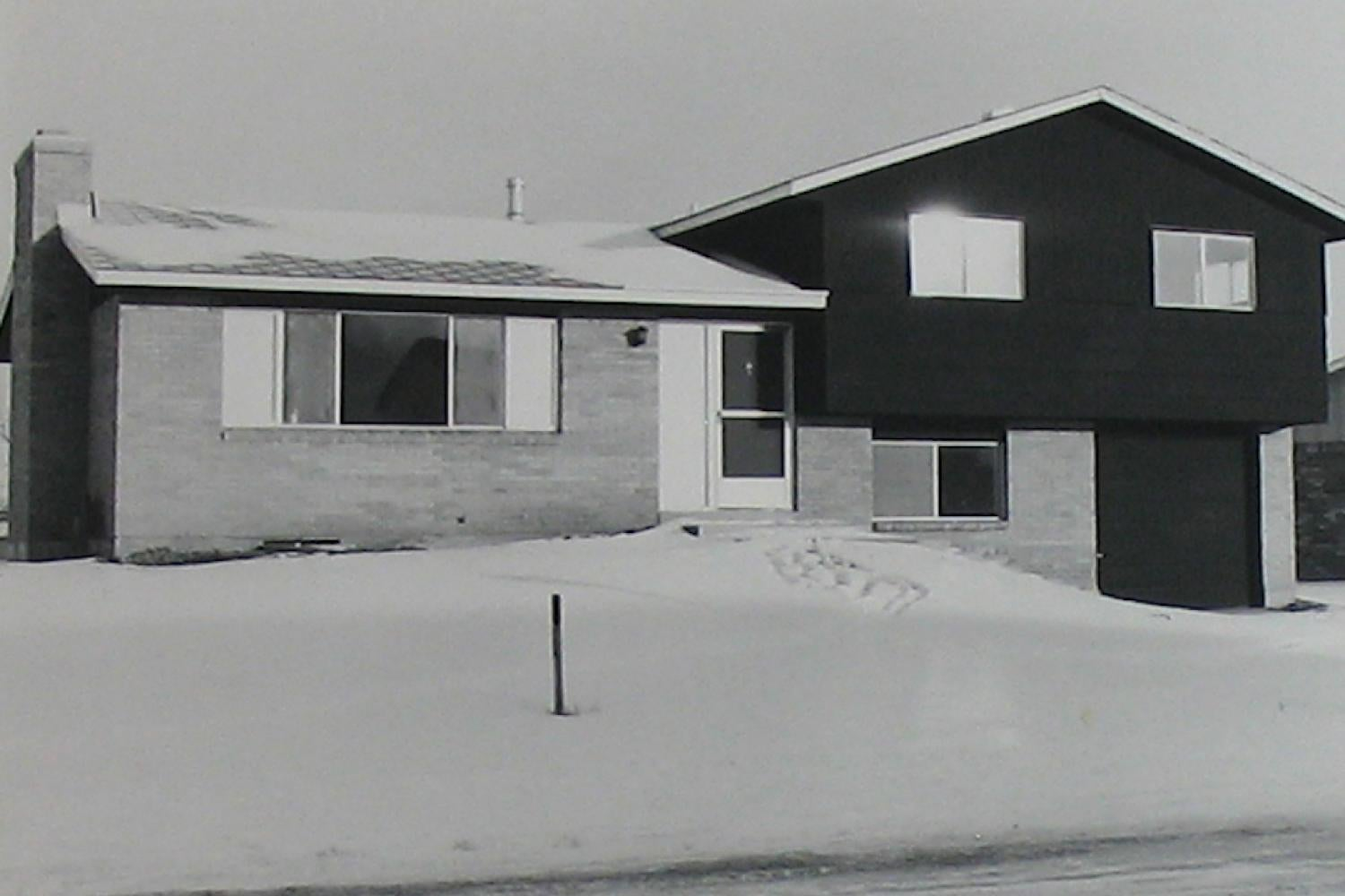 black and white photograph of a split level suburban home
