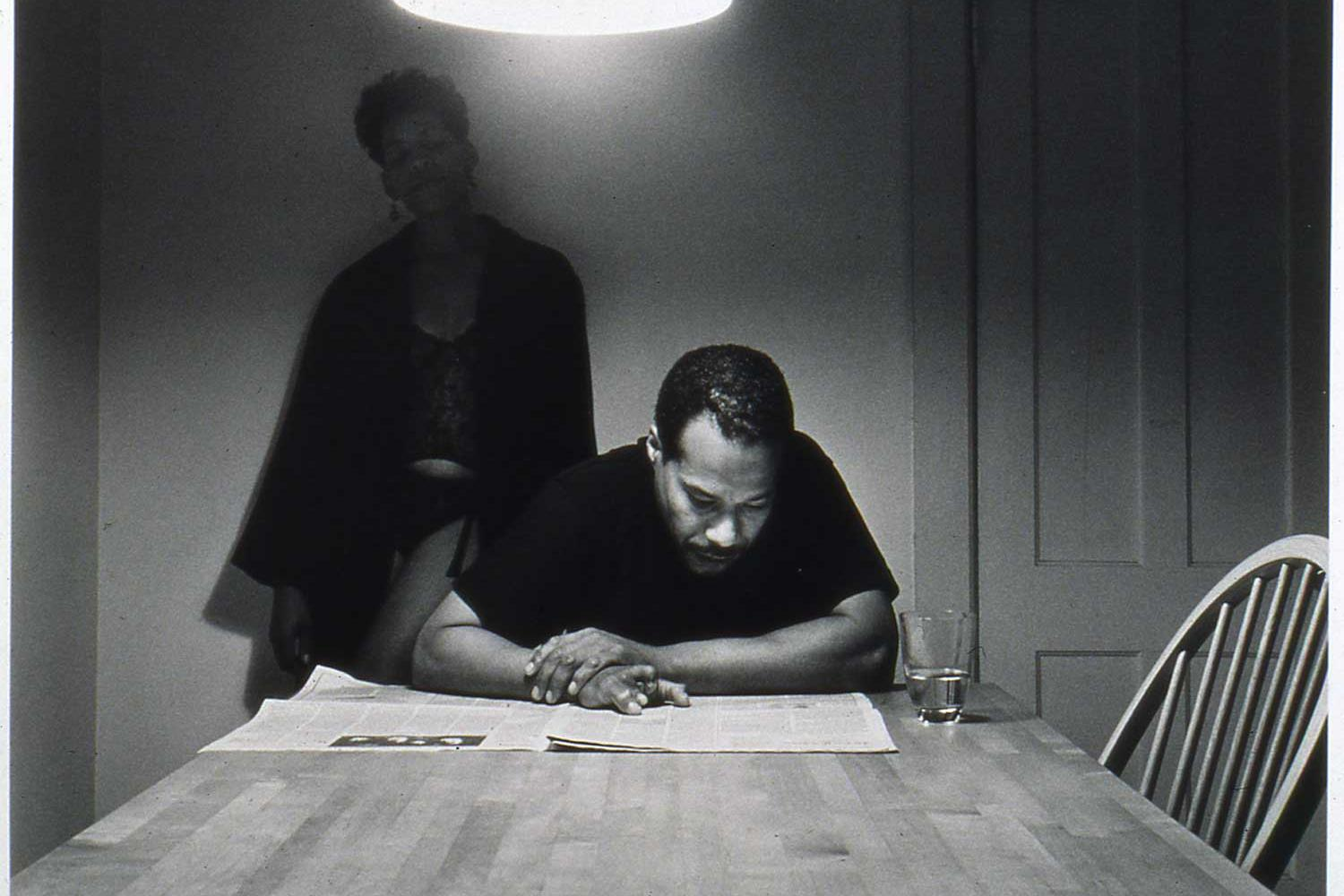 two african american figures, a man and a woman, at a kitchen table