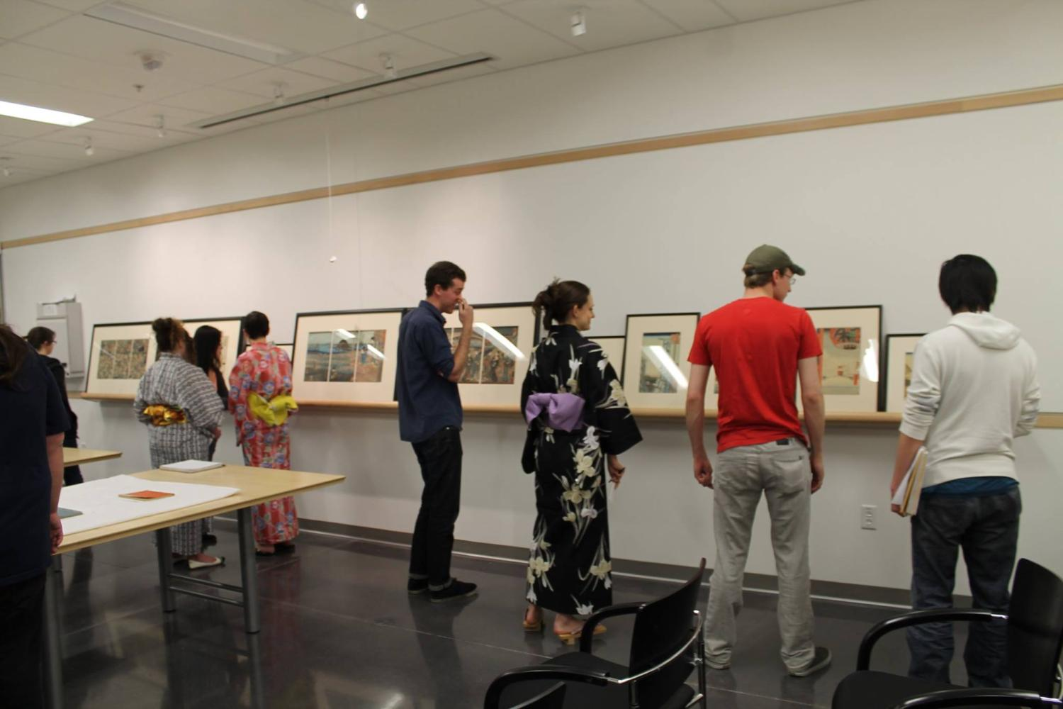 Students, some wearing kimonos, view framed prints.