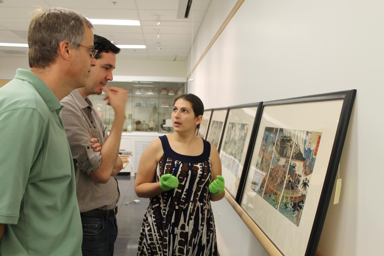 Two male professors converse with a female student while looking at a framed Japanese print.