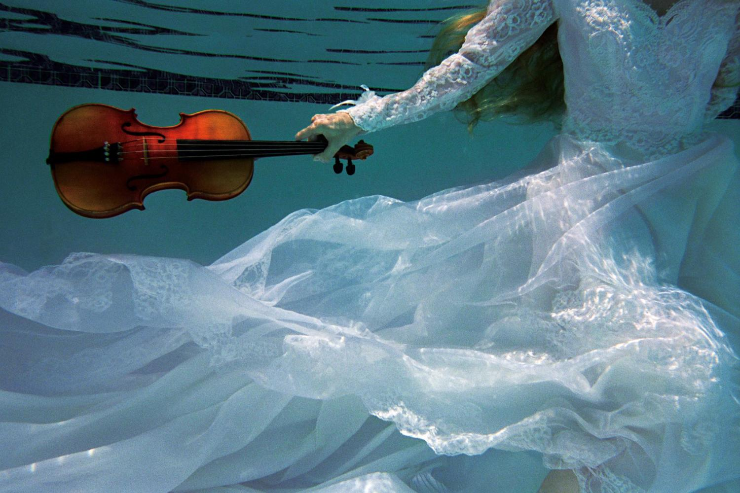 A figure in a white dress underwater hold a violin in their left hand