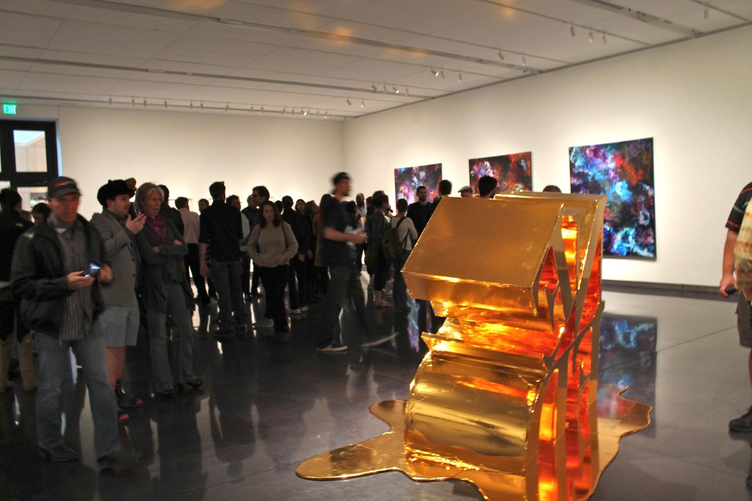A crowd mingles in the gallery with a large gold sculpture in the foreground.