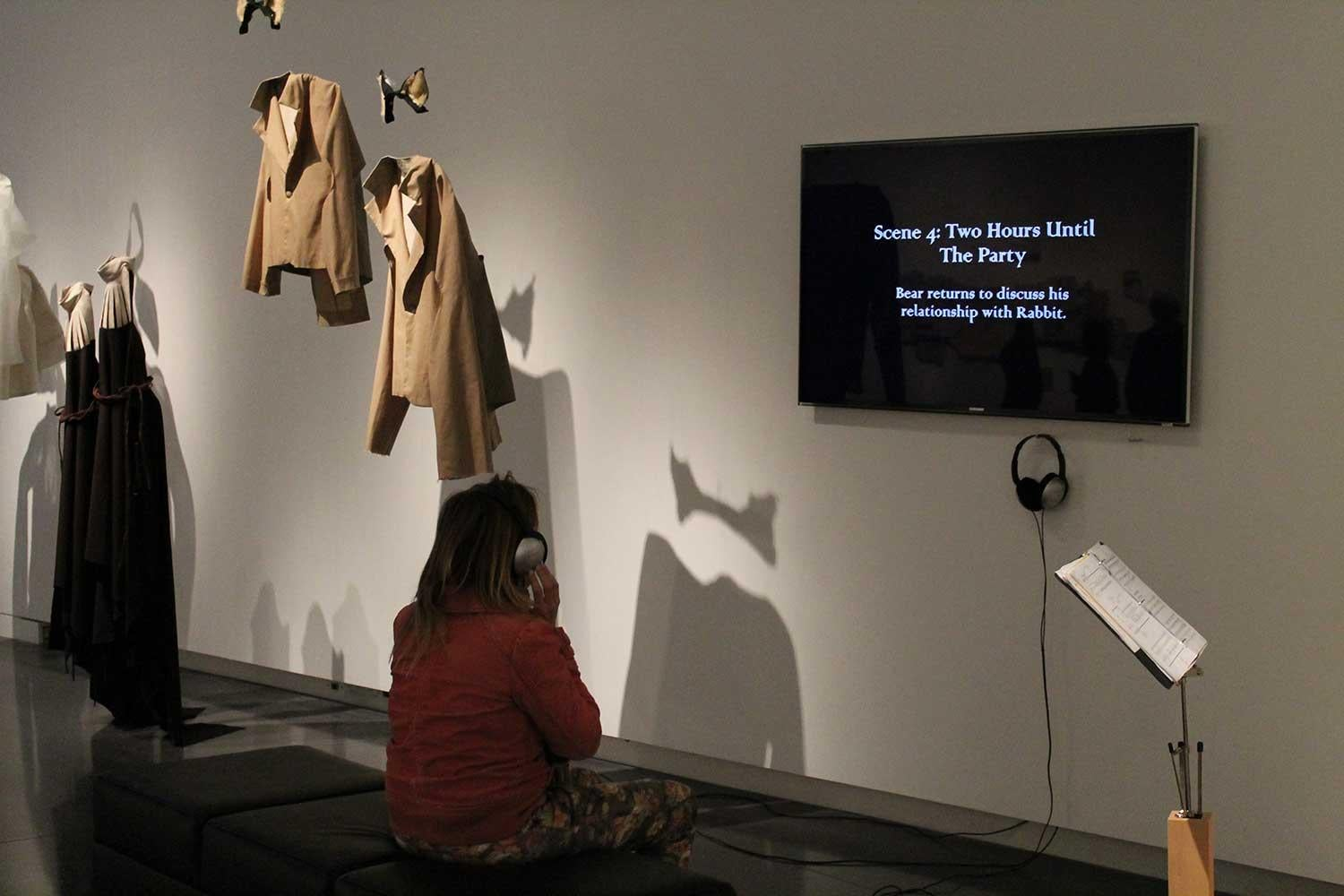 clothing and a screen hung on a wall as a part of an installation