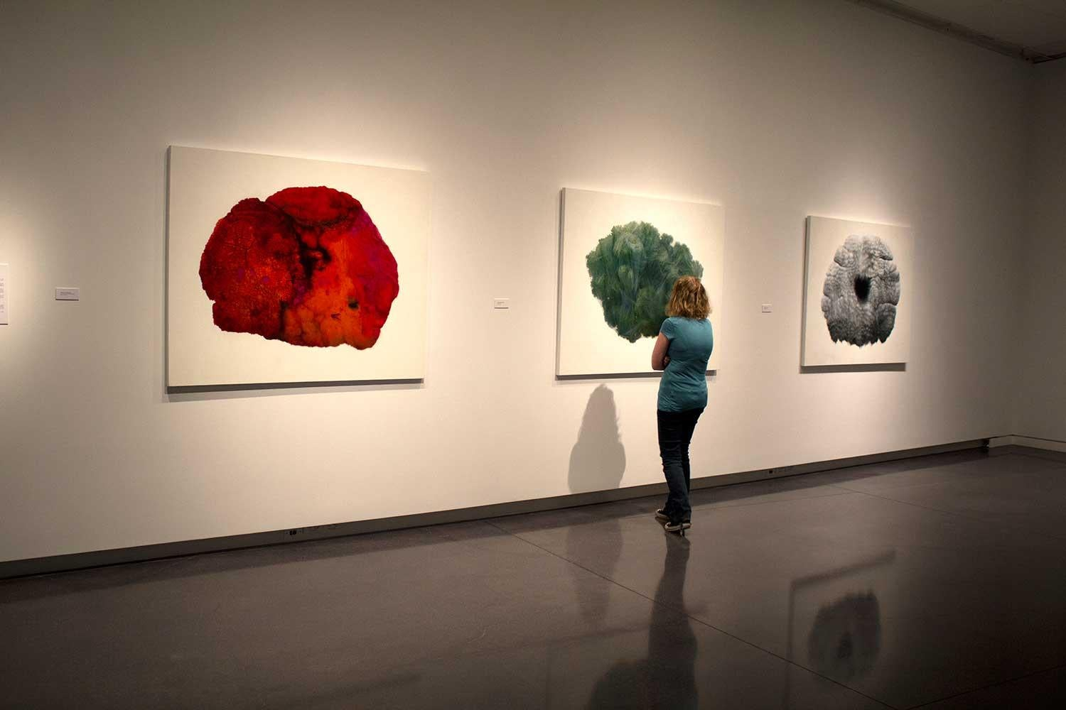a woman stands in front of three large drawings hanging on the wall, one is red, one is green, on is grey