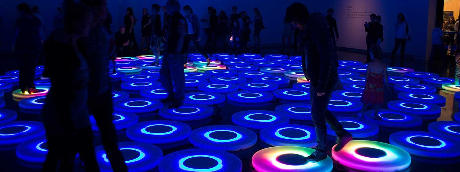 People walking on light-up pods on the floor of the gallery