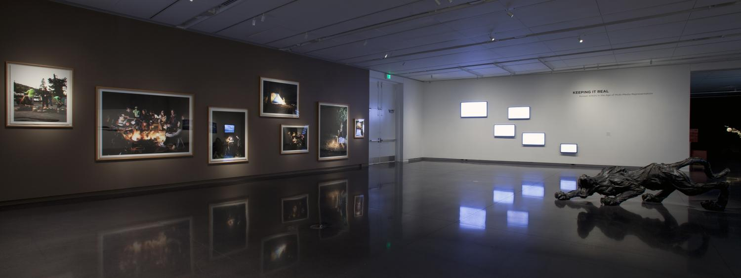 Framed photographs on gallery wall with large panther sculpture on gallery floor