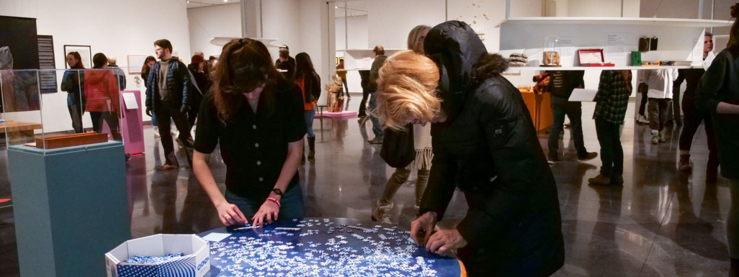 Photo of the inside of a museum gallery with many people looking at art. In the foreground two people are putting together a puzzle.