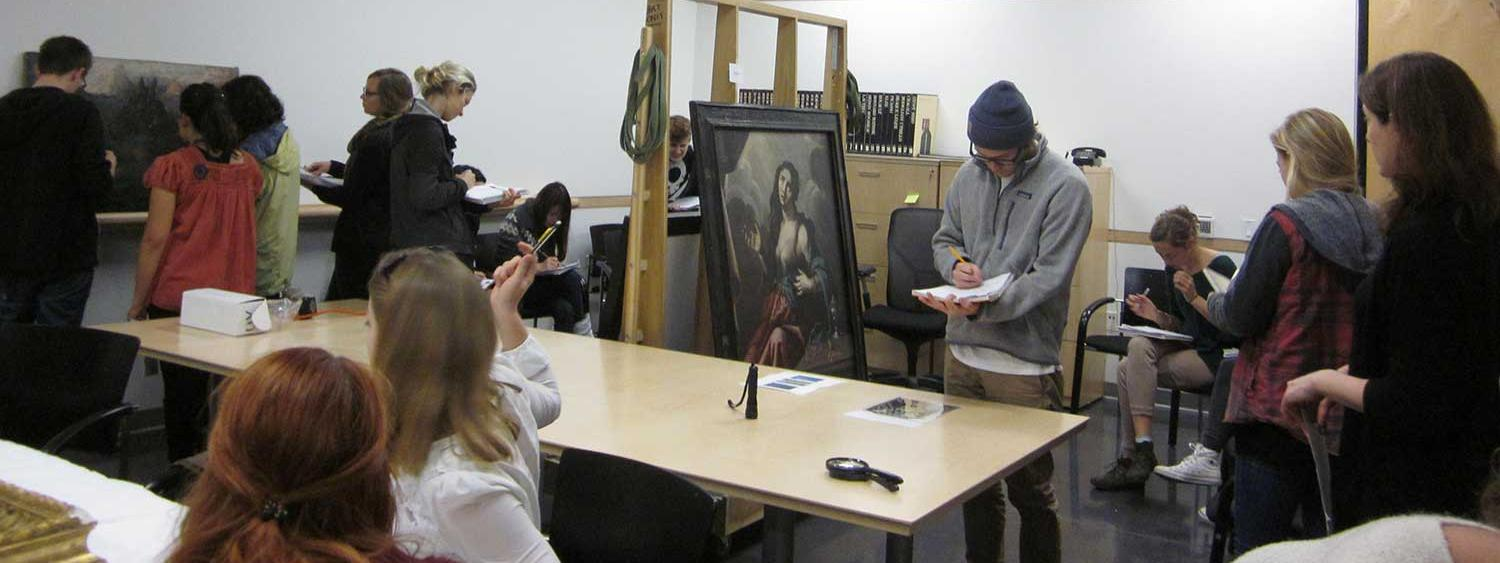 Students study a painting on an A-frame rack