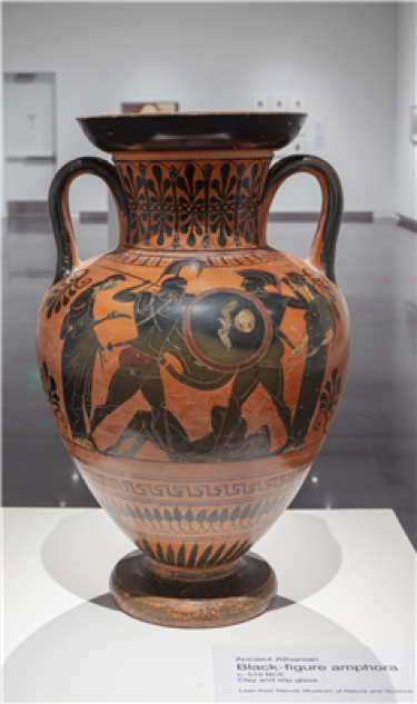 An amphora with black figures on either side. The vessel is mostly reddish and there is a variety of black decoration throughout.