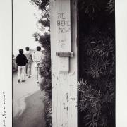 Black and white photo of white fence post with BE HERE NOW carved into the side
