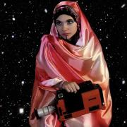 Woman with body and head covered but face shown standing in front of starry background and holding video camera