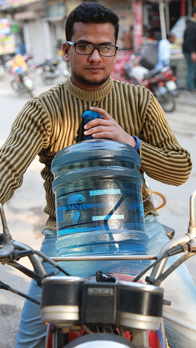 Guy with large container of water on a motorcycle