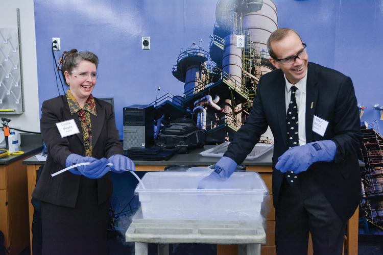 "Chevron's Cynthia Murphy and Mike Wirth cut a ""ribbon"" during the naming of the Chemical and Biological Chevron Lab."