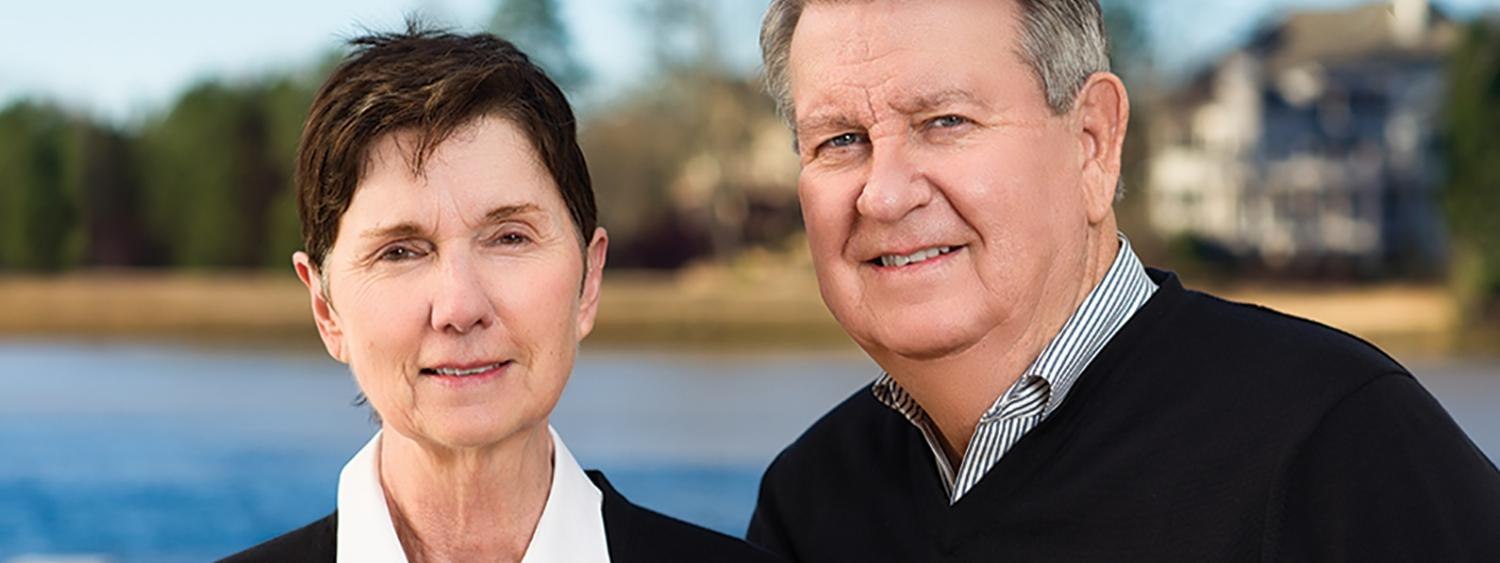 David and Debbie DeCook smiling and posing for the camera in front of a lake out back of their home in Georgia.