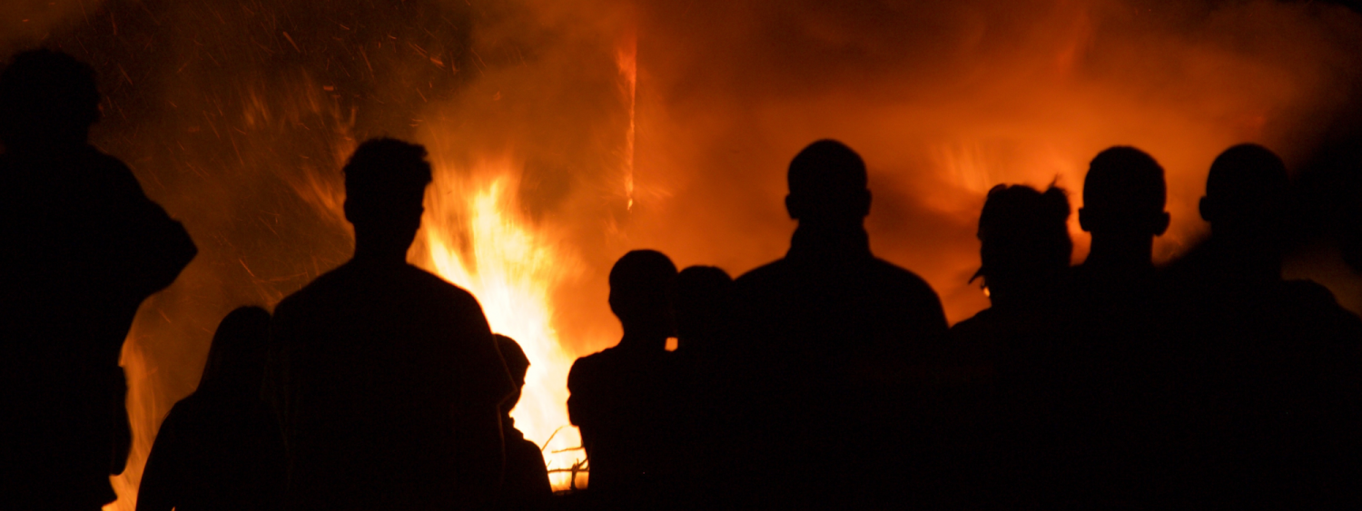 Silhouette of firefighters in front of a blaze