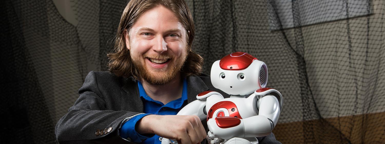 Dan Szafir sitting with a robot