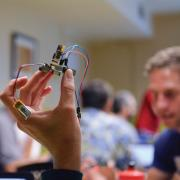 close up of a small device being held between a few fingers, blurred background of people.