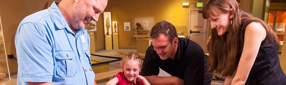 Family gathered around a table looking at a museum object