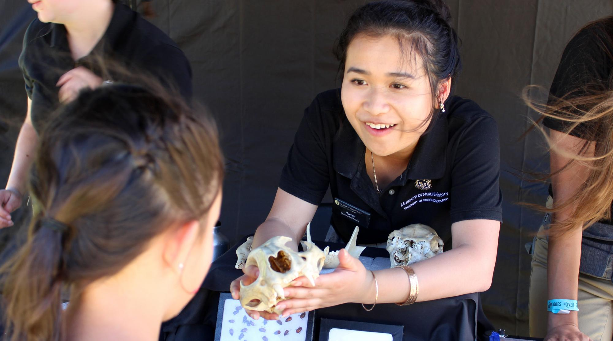 student showing animal skull to museum visitor