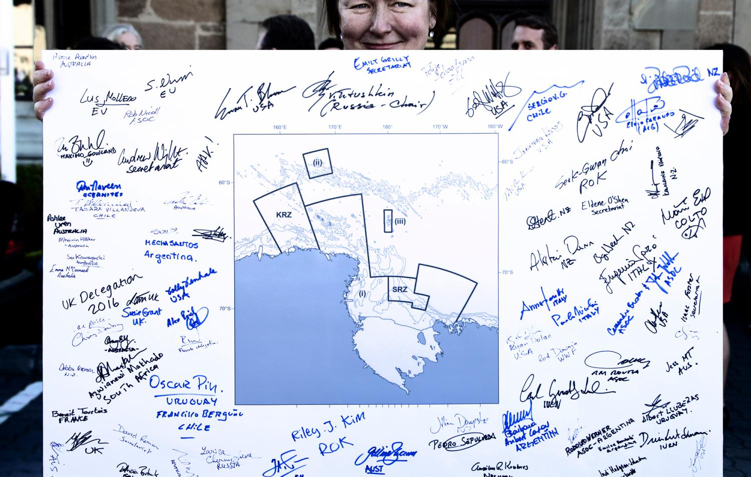 Woman holding map of Marine Protected Area with signatures on it.
