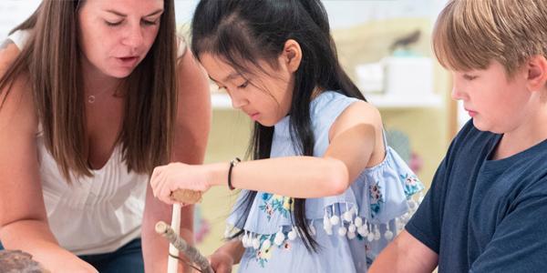 museum volunteer showing artifact to young children