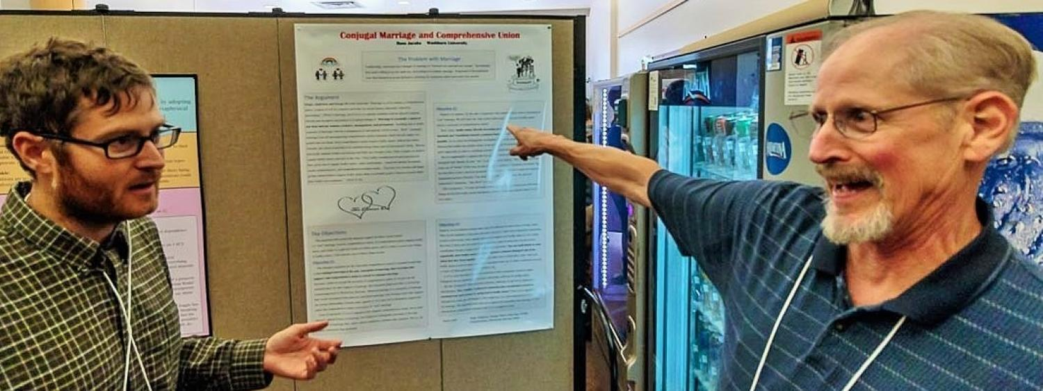 CU graduate student Spencer Case and Russ Jacobs (Washburn University) debating the nature of marriage during the poster session at CVSP's Rocky Mountain Ethics Congress VIII