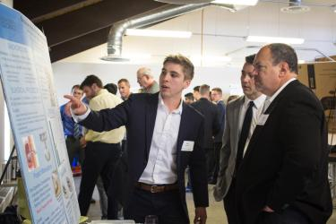 Senior design students presenting their work to an industry member