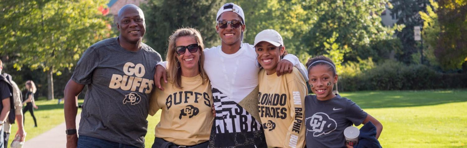 a family in Buffs gear posing on campus