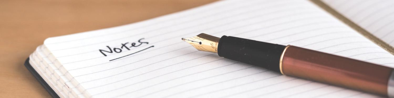"A pen laying on an open notebook with the word ""note"" written on the page."