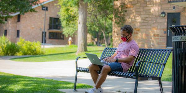 student on laptop in the quad