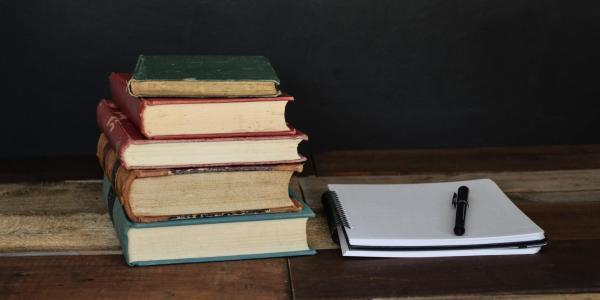 books sitting beside a notebook